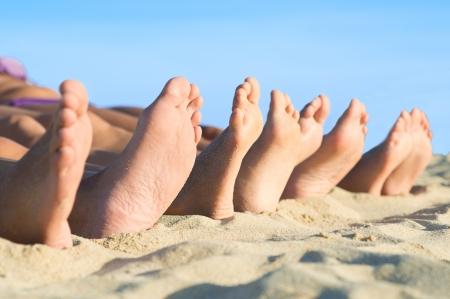 pies masculinos: Primer plano de la fila pies acostado en fila en la playa de verano Foto de archivo