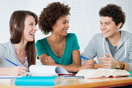 Group Of Young Cheerful Friends Studying Together Their Homework  photo