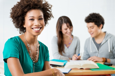 Happy Female Student Smiling And Looking At Camera In Class  photo
