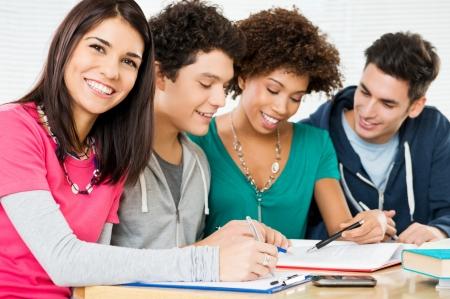 estudiando: Feliz grupo de jóvenes estudiantes que estudian juntos en la biblioteca