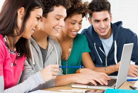 student desk: Group of Happy Friends Working On Laptop in Class  Stock Photo