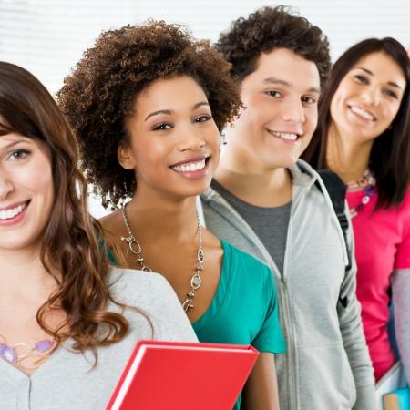 jovenes: Los estudiantes feliz de pie en fila y Mirando a la c�mara sonriendo