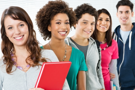 hispanic americans: Happy Smiling Students Standing In Row  Stock Photo