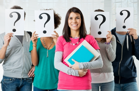 people problems: Woman Standing In Front Of Friends Holding Paper With Question Mark Signs