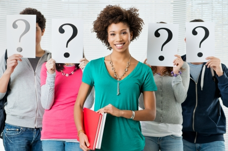 certain: Young Woman Standing In Front Of Friends Holding Paper With Question Marks