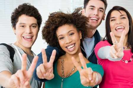 Happy Young students Showing Victory Sign  photo