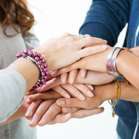 segítség: Csoport tizenéves Stacking kezükben, egység és szolidaritás