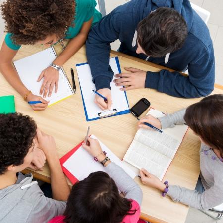 estudiando: Grupo de jóvenes estudiantes que estudian juntos en la universidad, ángulo de visión de alta