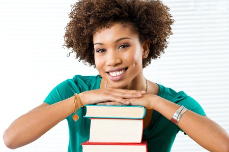 Portrait Of Happy African Student Leaning On Books  photo