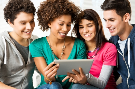 jovenes: J�venes Amigos felices jugando y mirando Tableta digital