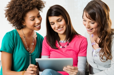 multi ethnic groups: Happy Young Beautiful Women Looking and playing with Digital Tablet