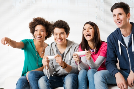 jugando videojuegos: Feliz grupo de j�venes amigos en los videojuegos en el hogar