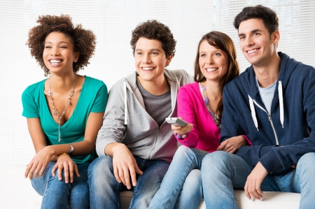 Happy Group Of Young Friends Watching Television At Home  photo