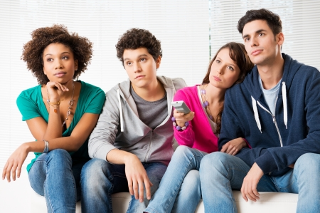Group Of Young Friends Watching Television with bored expressions  Stock Photo