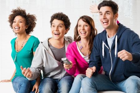 pareja viendo television: Feliz grupo de jóvenes amigos mirando la televisión y apoyar a su equipo