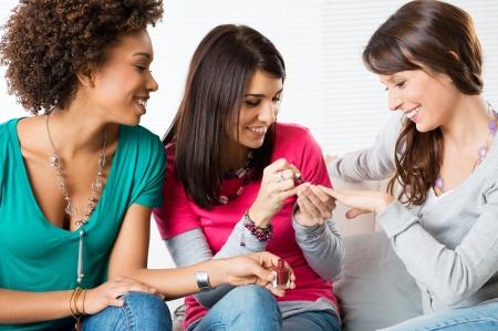 manicura: Retrato De Chicas J�venes Felices aplicaci�n de pintura de u�as mientras est� sentado en el sof� Foto de archivo