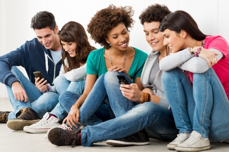 mobile: Group Of Happy Young Friends Looking At Cell Phone