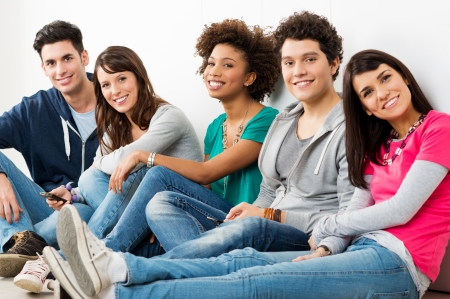 people in a row: Group Of Happy Smiling Friends Sitting In A Row indoor  Stock Photo
