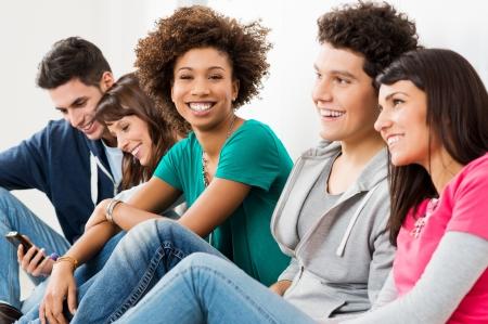 happy young: Grupo de amigos felices sonriendo sentado en una fila