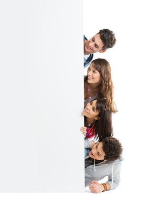Happy Smiling Group Of Teenager Isolated Looking At Blank Placard Board