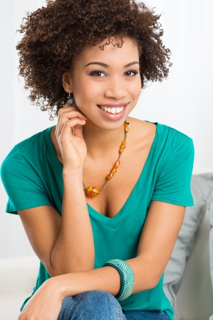 african woman face: Portrait Of Young Girl Sitting On Couch