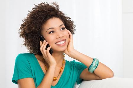 Portret van jong meisje praten over de telefoon zit op de bank Stockfoto