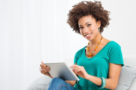 Portrait Of Young Happy African Woman Using Digital Tablet photo