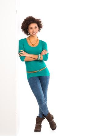 black girl: Happy Young Woman Isoliert Gelehnt einem Panel auf weißem Hintergrund Lizenzfreie Bilder