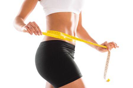 허리의 잘룩 한 선: 흰색 배경에 그녀의 허리의 잘록한 곳을 측정하는 젊은 여성