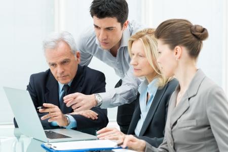 tecnologia: Equipe dos executivos que trabalham juntos em um laptop