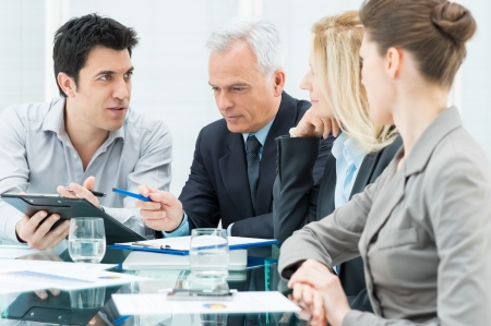 explain: Group Of Coworkers Discussing In Conference Room Stock Photo
