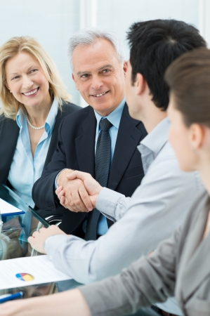 happy business team: Successful Business Executives Shaking Hands With Each Other
