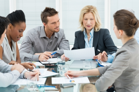 discussion group: Group Of Coworkers Discussing In Conference Room Stock Photo