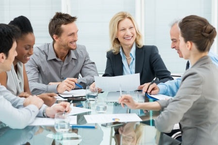 team meeting: Group Of Happy Coworkers Discussing In Conference Room Stock Photo