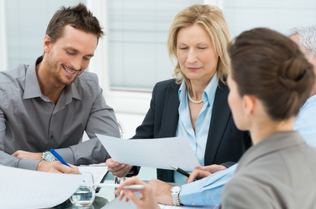 Boardroom meeting: Group Of Happy Coworkers Discussing In Office