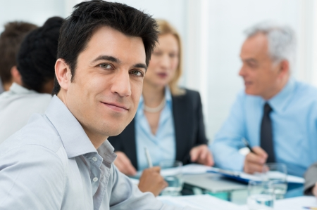 Boardroom meeting: Portrait Of Happy Young Businessman Working In Office