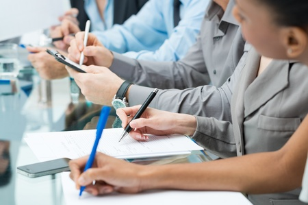 Close-up Of A Business People Hands Writing Note During Meeting photo