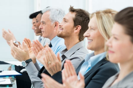applauding: Businesspeople In A Row Greets With Clapping Hands Stock Photo