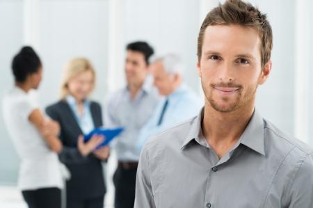lider: Retrato del hombre de negocios hermoso joven en oficina con los colegas en el fondo