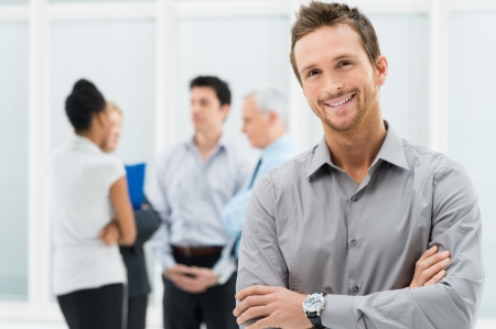 skill: Portrait Of Young Handsome Businessman Smiling In Office Stock Photo