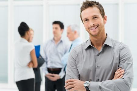 Portret młody przystojny biznesmen uśmiecha się w biurze
