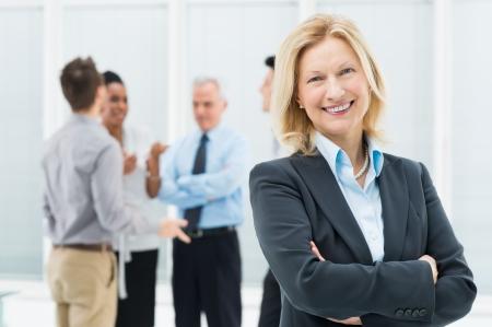 magabiztos: Portré a boldog vezető üzletasszony hivatalban kollégáival