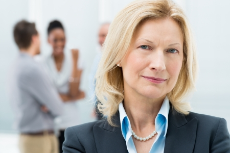 woman mature: Portrait Of Happy Senior Businesswoman In Office