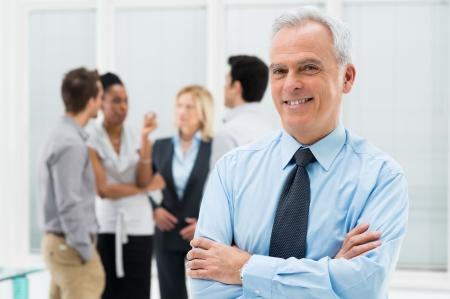 Portrait de l'heureux homme d'affaires senior dans son bureau avec des collègues