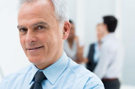 associates: Close-up Portrait Of Happy Senior Businessman in His Office Stock Photo