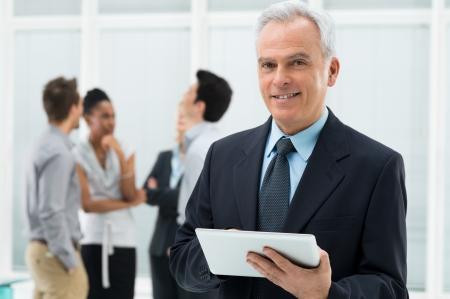 IT: Portrait Of Senior Businessman Holding Digital Tablet at Office Stock Photo