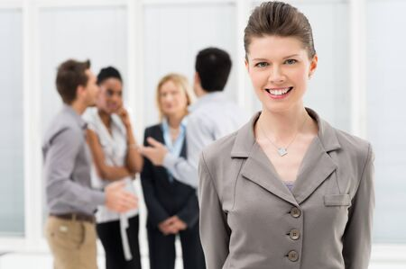 proud: Portrait Of Young Businesswoman Standing In Front Of Co-workers at Office