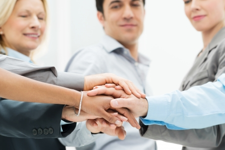 community work: Group Of Businesspeople With Stacked Hands Showing Unity and Teamwork Stock Photo