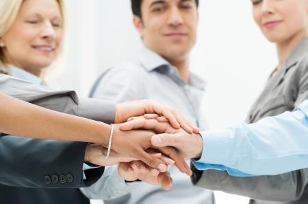 la union hace la fuerza: Grupo de empresarios con las manos apilados muestran la unidad y trabajo en equipo