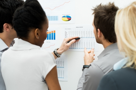 account: Group Of Business People Analyzing Graph and Annual Report Stock Photo
